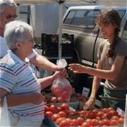 Woman Handing Bag of Tomatoes to Farmers' Market Vendor