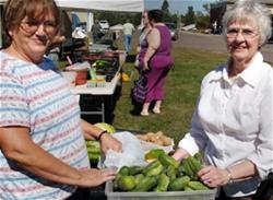 Women Exchange Cucumbers at Local Farmers' Market