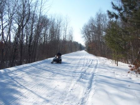Snow Mobile on Trail in Woods