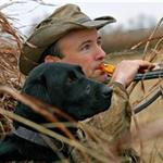 Duck calling man and black lab